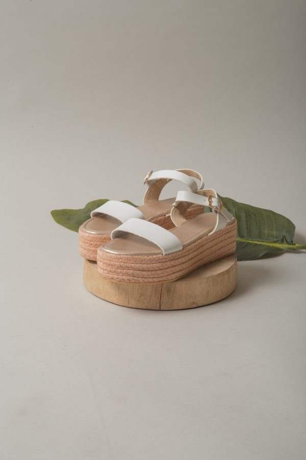 A product shot of flatbed shoes on a wooden stand