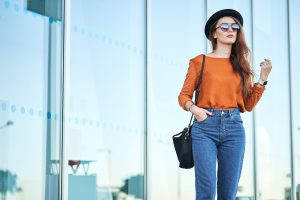 Young woman in a stylish outfit complete with a hat and shades