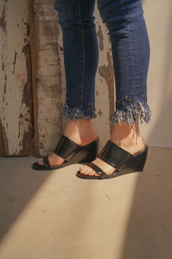 A woman standing in jeans with wedge shoes