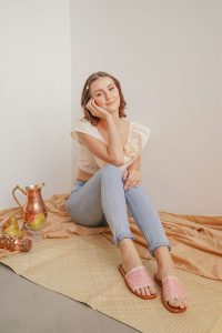 A girl sitting on the floor wearing sandals