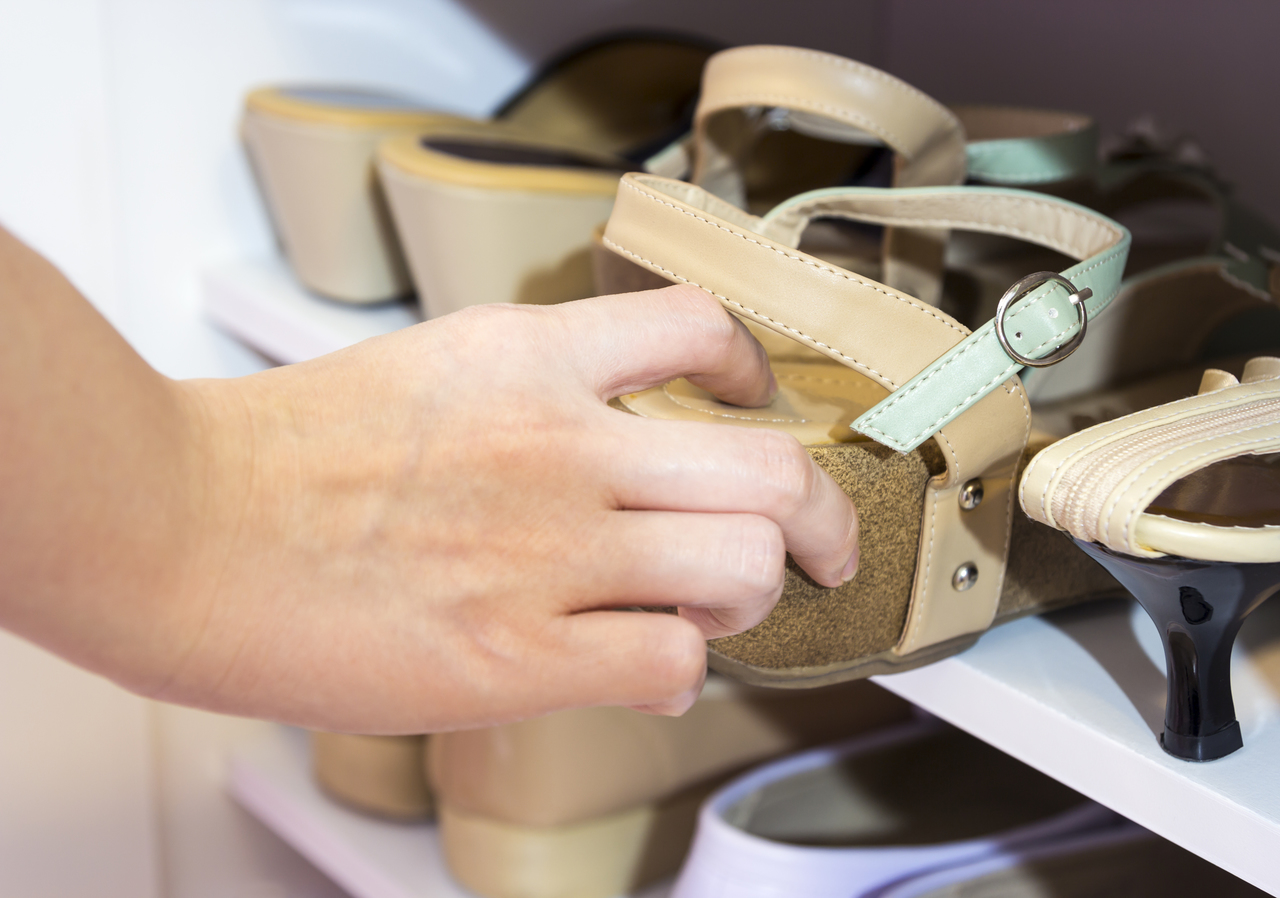 A woman taking sandals out of the shoe rack
