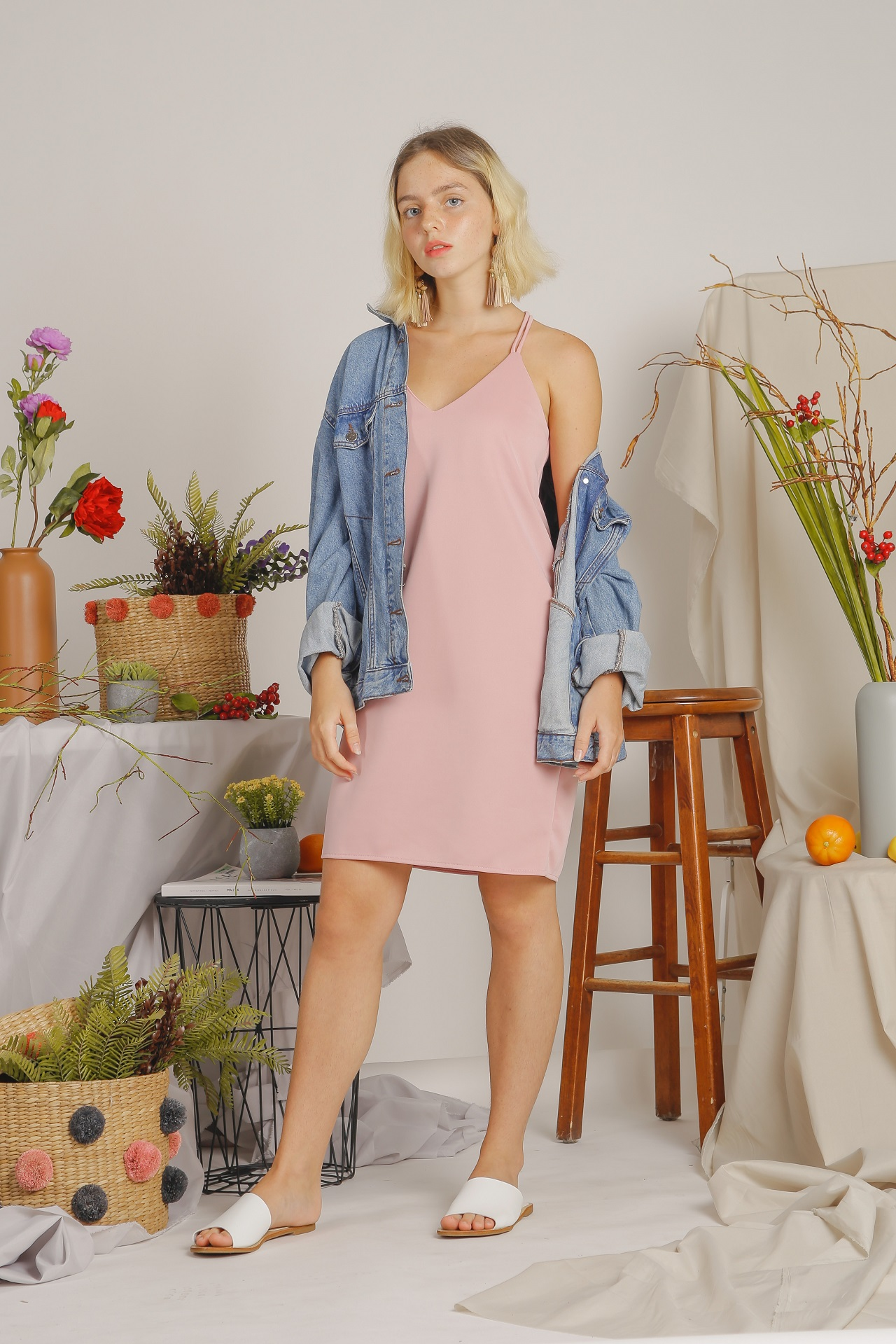 A girl wearing a dress, a denim jacket, and sandals