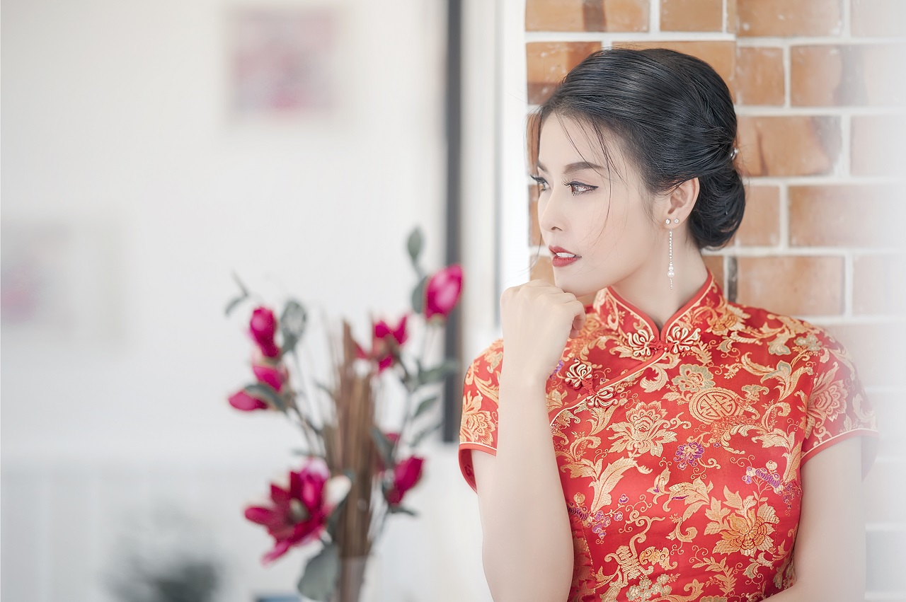 A Chinese woman reading a red dress