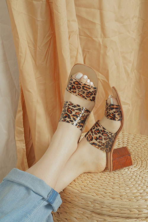 Close up of crossed feet wearing leopard print sandals