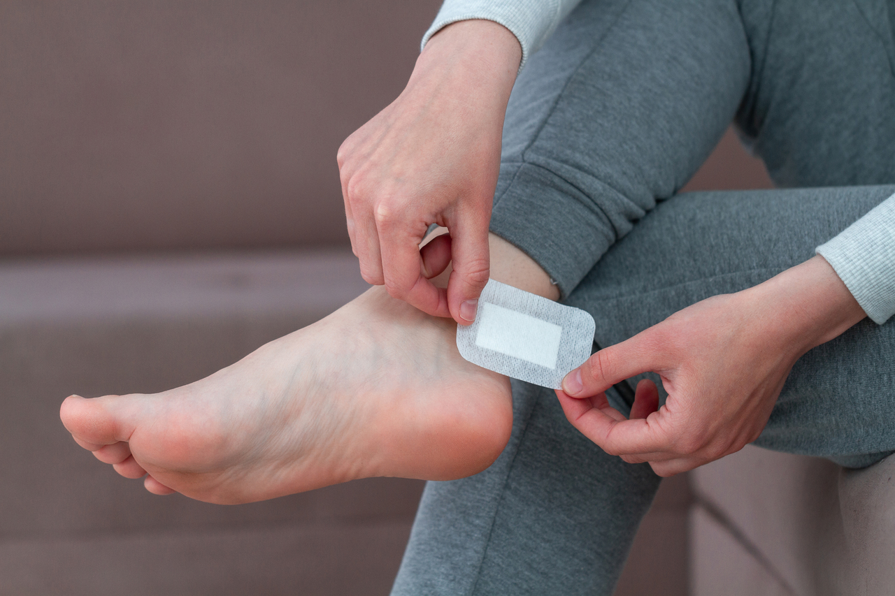 A woman placing a bandaid on her foot blister